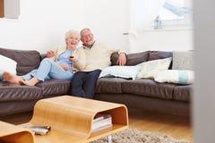 资深夫妇坐看电视的沙发 库存图片