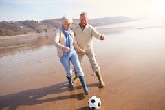 踢在冬天海滩的资深夫妇橄榄球 库存图片