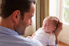 Πατέρας στο σπίτι με τη νεογέννητη κόρη μωρών ύπνου Στοκ εικόνα με δικαίωμα ελεύθερης χρήσης
