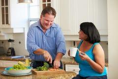 在准备菜的饮食的超重夫妇在厨房里 免版税库存照片