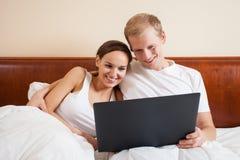 愉快的夫妇在与膝上型计算机的床上 免版税库存照片