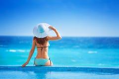 从后面的妇女有白色帽子的坐海岸 库存照片