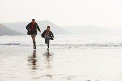 跑在与捕鱼网的冬天海滩的父亲和儿子 免版税图库摄影