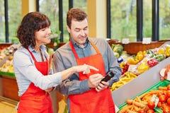商店经理显示职员如何使用数据终端 图库摄影