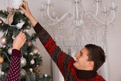 装饰圣诞树的愉快的年轻人 免版税库存图片