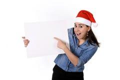 在圣诞老人圣诞节帽子指向空白的广告牌的年轻甜拉丁妇女 库存照片