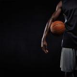 站立与篮子球的黑人蓝球运动员 免版税图库摄影