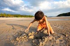 男孩获得户外使用在沙子由海滩的乐趣在日落 免版税库存照片