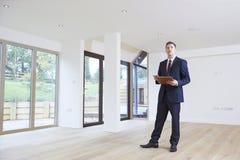Агент по продаже недвижимости смотря вокруг вакантного свойства для валюации Стоковое Изображение