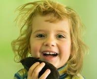有玩具的微笑的白肤金发的女孩在手中 免版税图库摄影