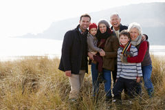 在沙丘的多一代家庭在冬天海滩 免版税库存图片