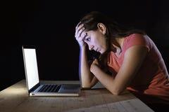 沮丧的工作者或学生妇女与计算机单独夜间一起使用在重音 免版税库存照片