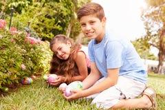 两个孩子有复活节彩蛋狩猎在庭院 库存图片