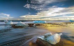 在岸的熔化的冰山在日落 免版税库存图片