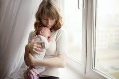 有逗人喜爱的矮小的哭泣的婴孩的母亲 免版税库存照片