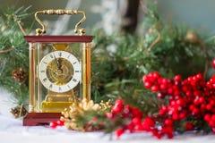 与教练,红色莓果和几个小时云杉的分支的圣诞节和新年的静物画, 免版税库存照片