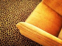 在豹子地毯的橙色天鹅绒扶手椅子 免版税库存照片