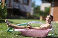 Мальчик с водой выплеска в горячем летнем дне Стоковые Фотографии RF