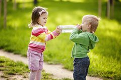 女孩帮助男孩保留瓶 免版税库存图片