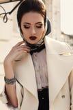 典雅的米黄外套和丝绸围巾的美丽的女孩在头 免版税库存图片