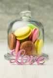 在一个玻璃钟形玻璃容器的多彩多姿的蛋白杏仁饼干 图库摄影