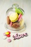 在一个玻璃钟形玻璃容器的多彩多姿的蛋白杏仁饼干 免版税库存照片