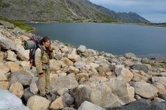 吃雪的旅游女孩在山湖附近 库存照片