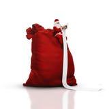 Санта сидя на большом мешке и читая длинный список Стоковое фото RF