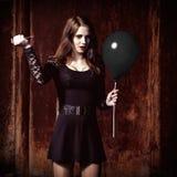 奇怪的恼怒的女孩由针刺穿一个黑气球 免版税库存照片