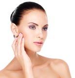 有新鲜的用手皮肤感人的面颊的妇女 库存图片
