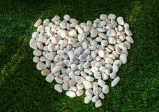 在心脏形状的石头,在草背景 免版税图库摄影