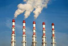 有白色烟的工业管子在蓝天 海岸线绿色水平的图象照片撒丁岛海运天空植被 免版税库存照片