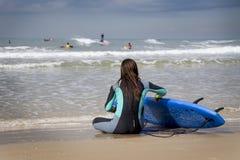 女性冲浪者坐海滩 免版税库存照片