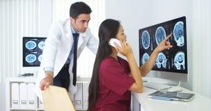 中国人护士谈话在智能手机在办公室 免版税库存图片