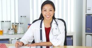 微笑对照相机的亚裔医生对书桌 免版税库存图片