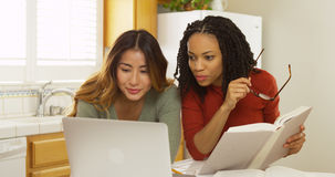 妇女大学生阅读书和使用便携式计算机学习 免版税图库摄影
