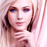 有桃红色丝绸的美丽的肉欲的妇女 免版税图库摄影