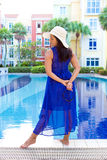 放松在充分的蓝色礼服的水池的白色太阳帽子的妇女 免版税图库摄影