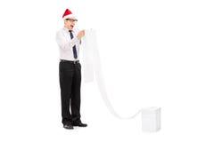 有圣诞老人帽子的激动的人读一张长的名单的 库存图片