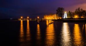 一致点灯塔和一个码头在晚上在格雷斯港 图库摄影