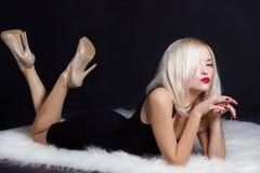 有明亮的构成红色嘴唇的美丽的性感的典雅的醒目的白肤金发的妇女在一件黑礼服在白色毛皮说谎在演播室 库存图片