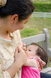 哺乳她的女婴的妈妈 库存照片