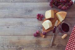 Κρασί, τυρί και σταφύλια στον ξύλινο πίνακα Άποψη άνωθεν με το διάστημα αντιγράφων Στοκ Φωτογραφία