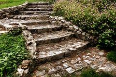 古色古香的鹅卵石楼梯在环境美化的庭院里 免版税库存照片