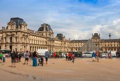罗浮宫的门面有走的游人和汽车的 免版税库存图片