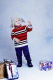 被编织的帽子和套头衫的愉快的小男孩有礼物盒的 免版税库存图片