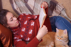 说谎在有红色猫的沙发和读a的女孩 库存照片