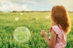 女孩吹的肥皂泡在夏天晴天 免版税库存照片