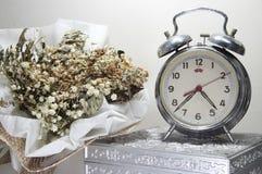 与残破的闹钟,死的花,老银色箱子的静物画 免版税库存图片