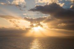剧烈的日落通过在海洋的多云黑暗的天空发出光线 免版税库存图片